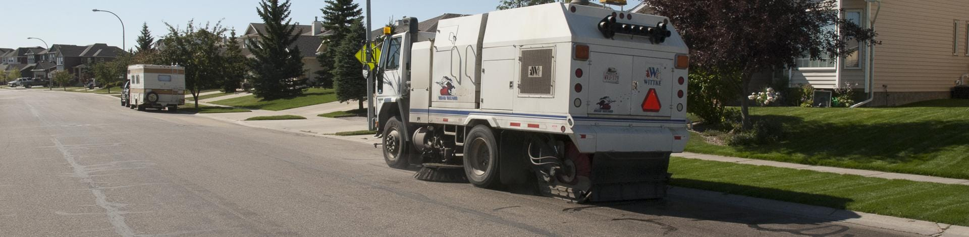 Street cleaning equipment in use in a residential area in Okotoks.