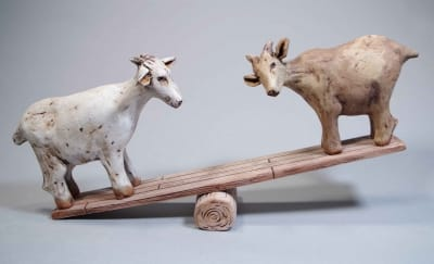 Two small clay goats balancing on a teeter totter