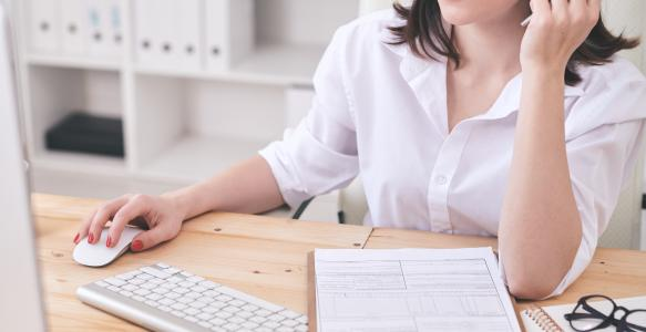Woman in home office at computer filing an online form