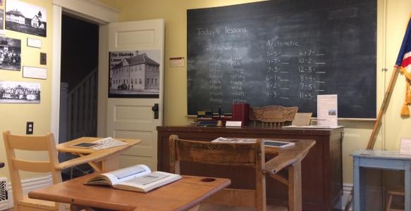 Photograph of an old-fashioned classroom with single-seat wooden desks and a chalkboard and flags.