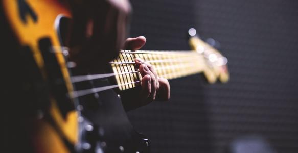 Close-up photo of two hands holding a guitar.