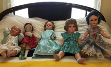 Five antique baby dolls lined up on an antique child's bed.