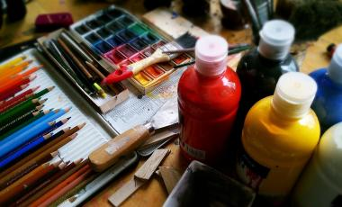 Pencils, paints, and art supplies on a wooden table.