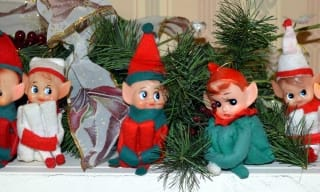 Toy elves sitting on a fireplace mantel