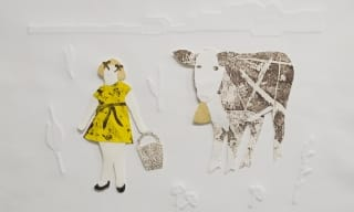 Paper cut out of a little girl with a cow