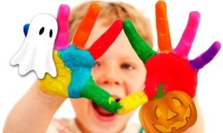 Toddler with paint on his hands, smiling, with cartoon ghost and pumpkin.