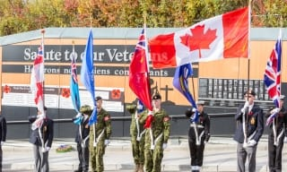 Colour party marching with flags in front of Veterans memorial wall