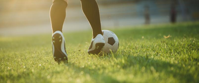 soccer player's feet dribbling ball across green soccer field