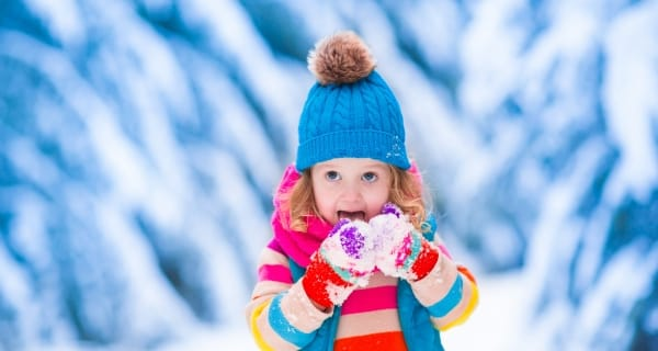 Child playing in snow in winter