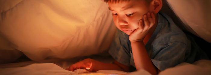 Child reading from their tablet device under the covers in their bedroom
