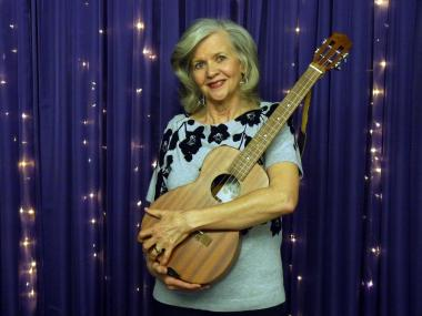 Dianne Harvey hugging a guitar in front of a sparkly purple curtain.