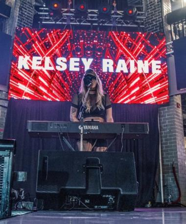Kelsey Raine on stage standing behind a keyboard piano.